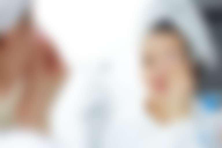 Довольная девушка в полотенце ватным диском протирает лицо