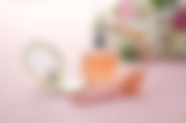 Флакон с духами и пульверизатором на фоне цветов