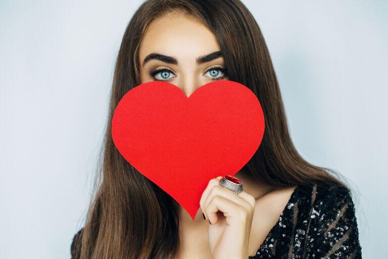 """Девушка прикрывает лицо красным """"сердечком"""""""