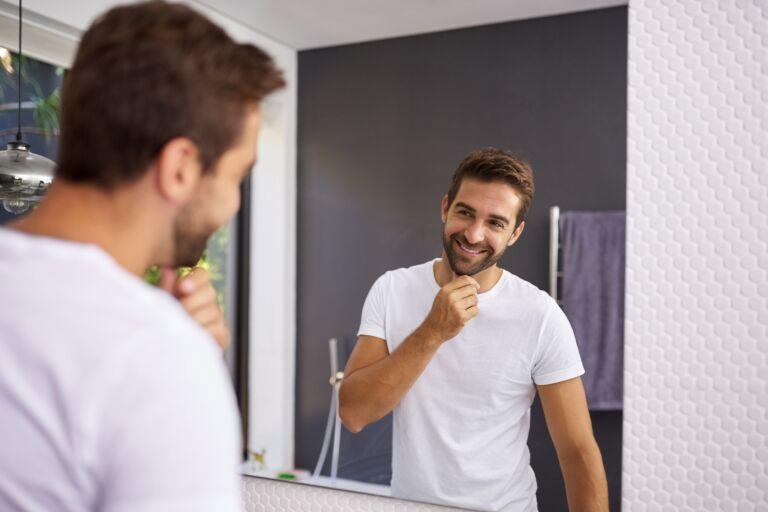 молодой парень рассматривает свое лицо в зеркало