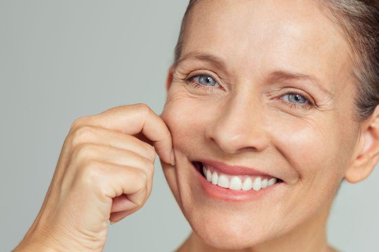 голубоглазая женщина улыбается и защипывает пальцами складку на щеке тест на упругость кожи
