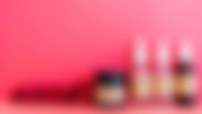 на ярко-розовом фоне красные хризантемы и косметика с витамином С, гиалуроновой кислотой, молочной кислотой и ретинолом
