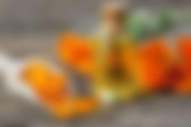 На столе разложены: цветки календулы, масла