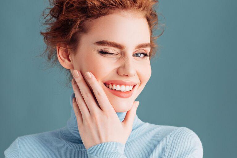 Подмигивающая рыжая девушка с белозубой улыбкой