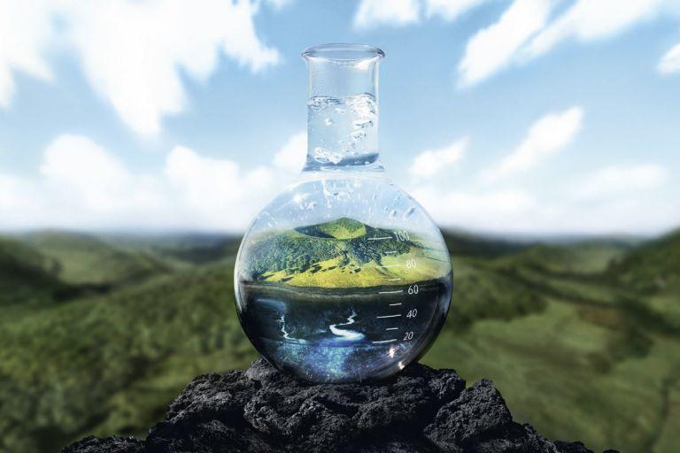 бутылочка с термальной водой стоит на вулканической породе среди зеленых холмов Овернь