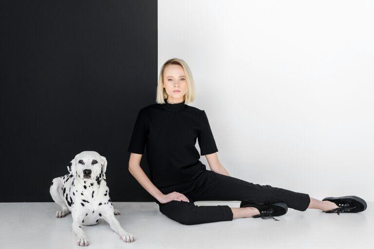 На черно-белом фоне сидят девушка в черной одежде и собака далматинец.