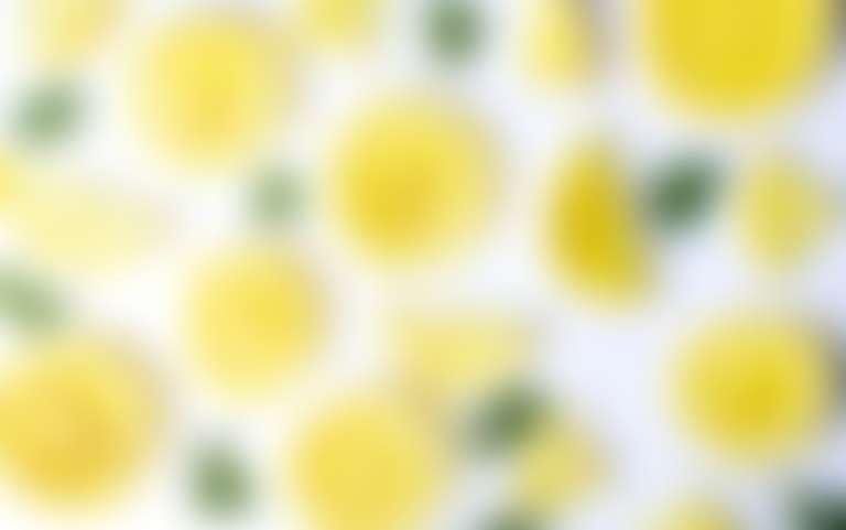 На столе разложен порезанный на дольки и кружочки лимон.
