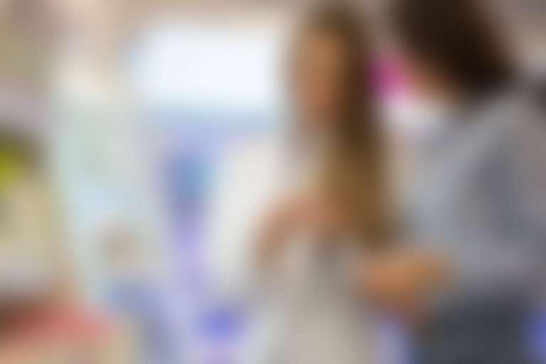 Девушка покупает сыворотку от пигментации под руководством консультанта в аптеке