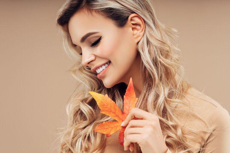 Улыбающаяся блондинка держит в руке осенний лист