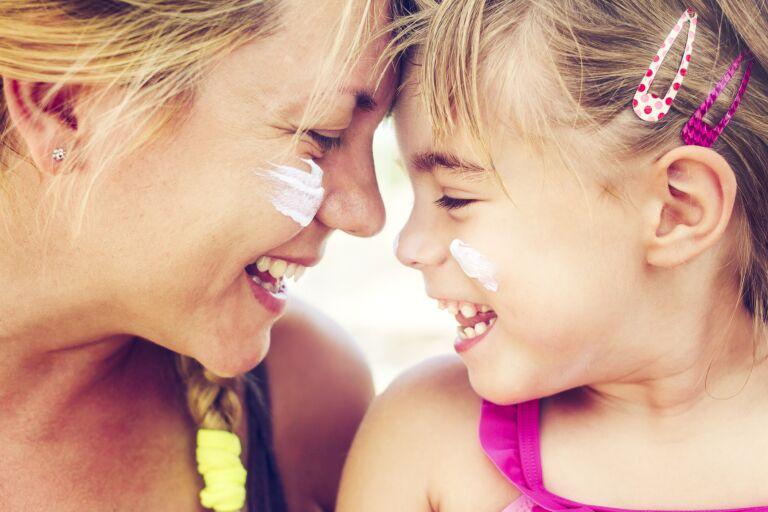 мама и дочка с мазками солнцезащитного крема на лице