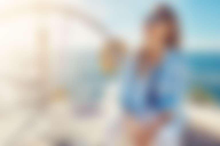 Девушка в голубой рубашке, морской футболке и темных очках сидит на белой яхте в открытом море и радостно смеется