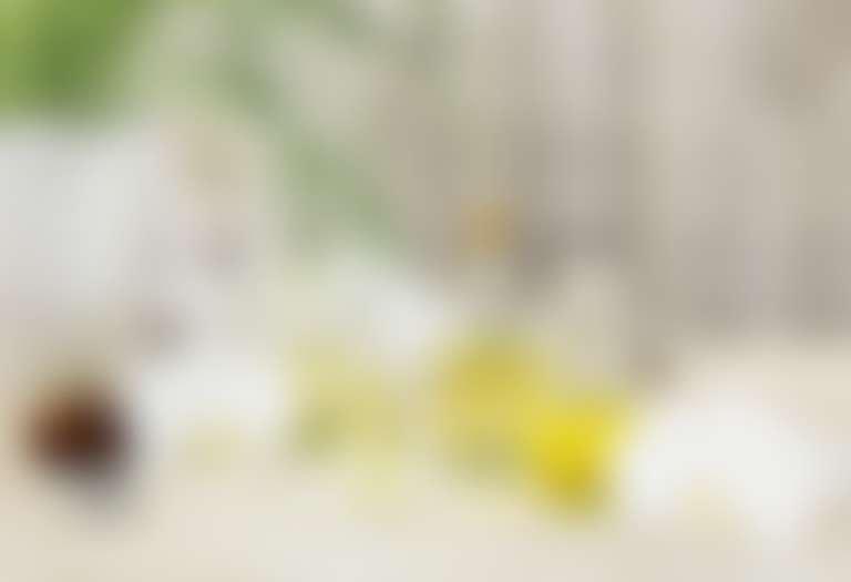 Масла в стеклянных колбах на белом столе, слева комнатное растение