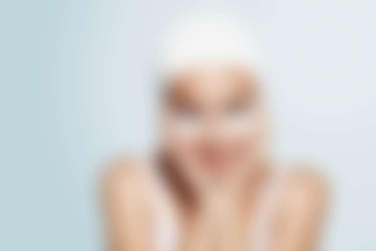 Девушка с белой повязкой на голове и патчами под глазами обхватила контуры лица руками
