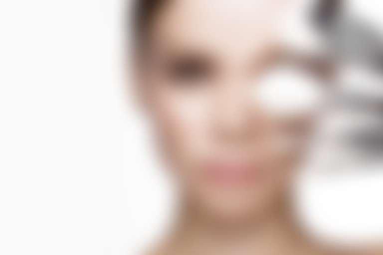 Девушка закрывает половину лица набором кистей для макияжа.