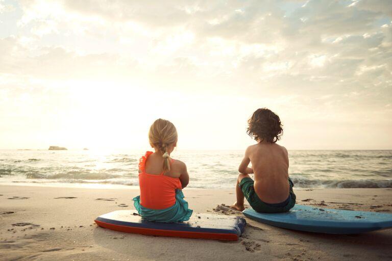 двое детей на закате сидят у моря