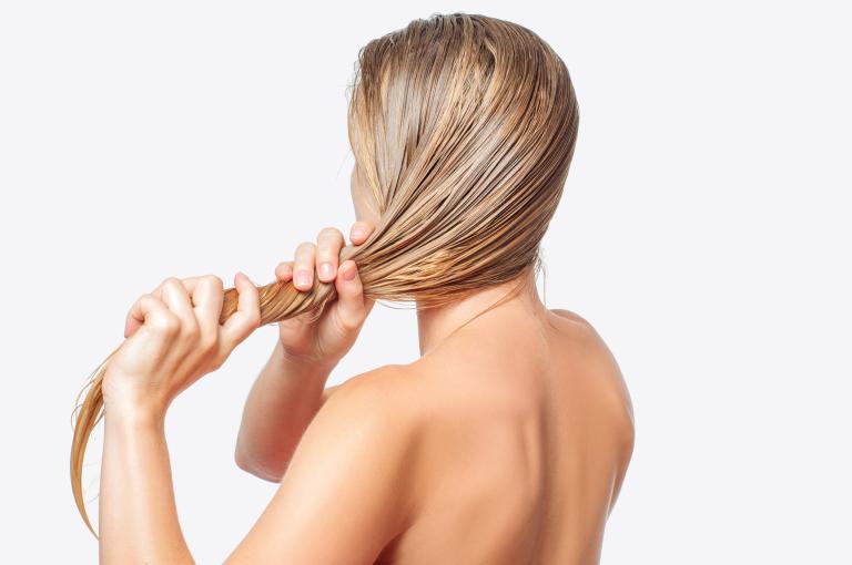 Девушка отжимает влажные волосы.