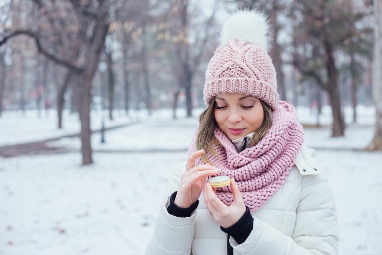 Девушка в зимнем парке наносит кокосовое масло на кожу губ.