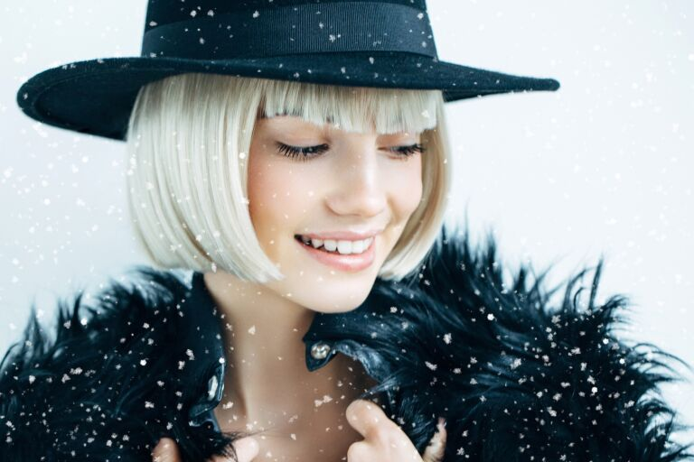 девушка с ухоженной кожей и светлыми волосами в черной шляпе и с меховым воротником на фоне снежинок