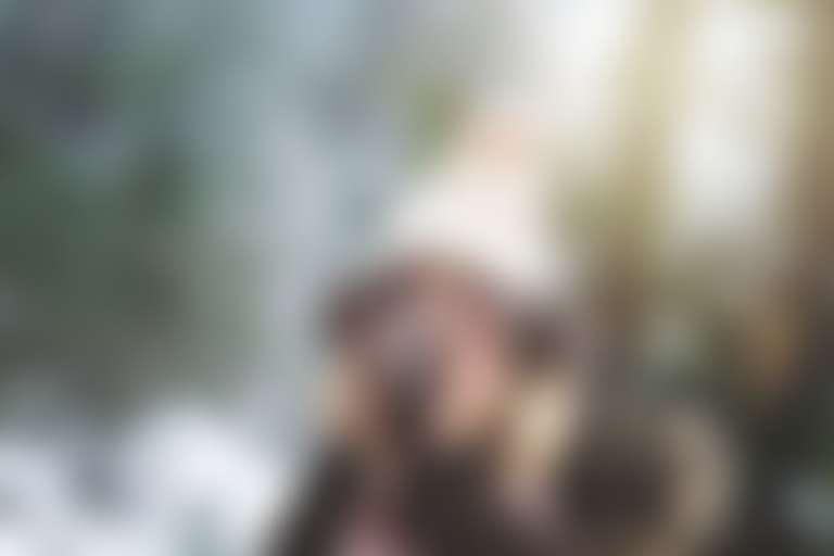 в зимнем лесу  девушка в шапке прижимает варежки к щекам