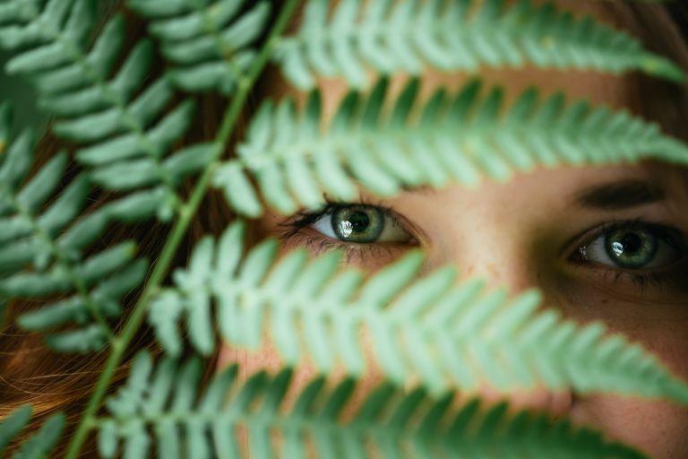 Женское лицо, частично скрытое листьями папоротника