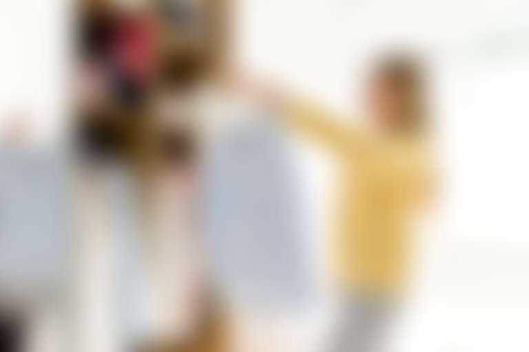 Девушка перед шкафом с одеждой выбирает блузки