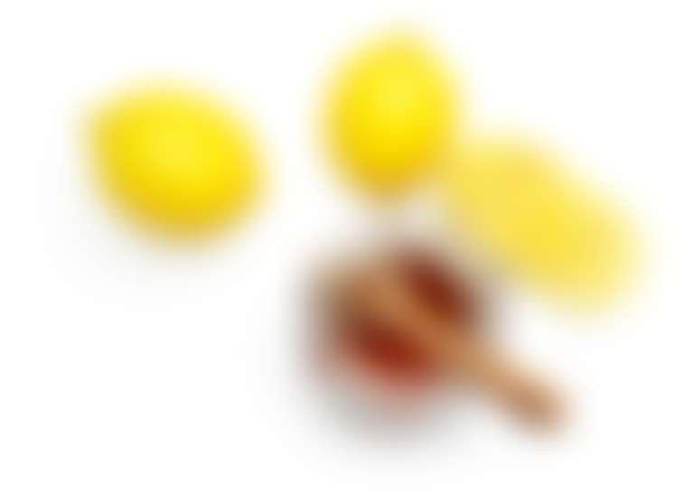 Открытая баночка меда с ложкой и лимоны