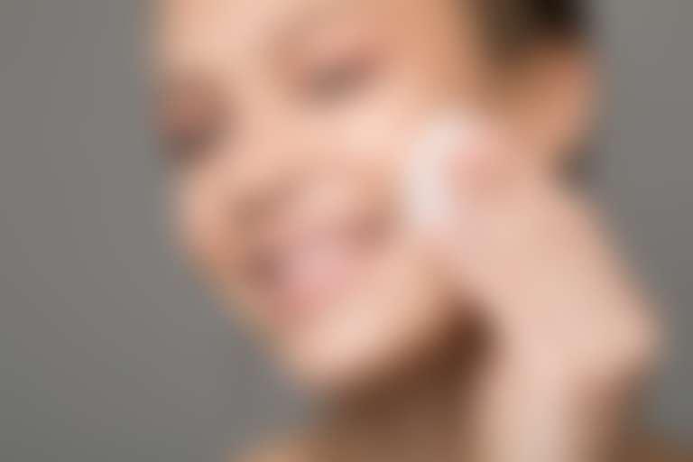 Довольная девушка смазывает лицо ватным диском, смоченным в тонике