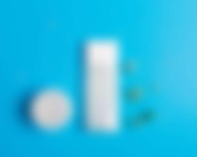 Пустая банка и пустой тюбик из-под косметических средств на сине фоне