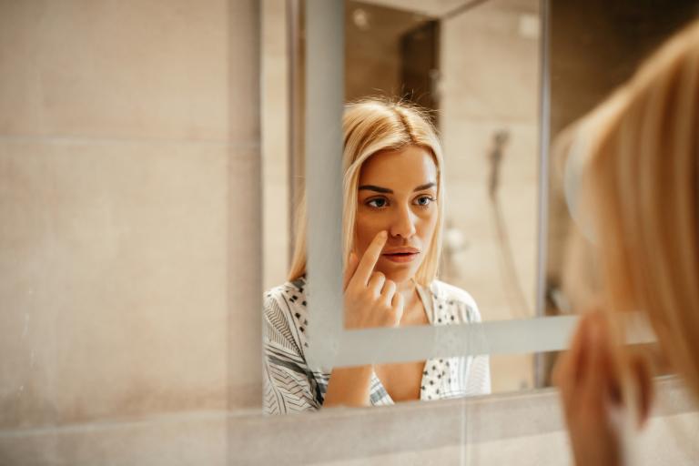 Девушка рассматривает в зеркале прыщи на коже.