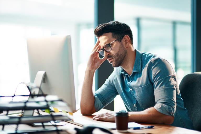 Мужчина с озабоченным лицом сидит перед монитором компьютера
