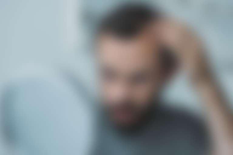 Мужчина с бородой смотрит на залысину в круглое зеркало