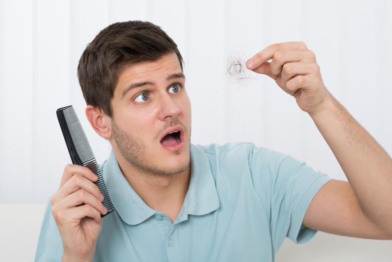 Молодой мужчина с расческой в руке, раскрыв рот, смотрит на клок волос