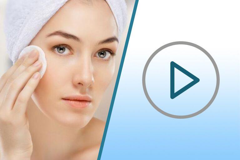 девушка с ухоженной кожей в тюрбане из белого махрового полотенца протирает ватным диском лицо