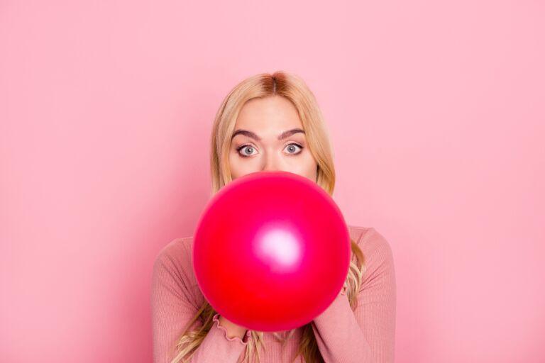 Блондинка на розовом фоне надувает красный воздушный шар