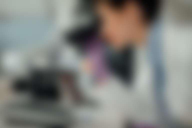 Девушка-лаборант в белом халате и с ярко-красной помадой смотрит, улыбаясь, в микроскоп