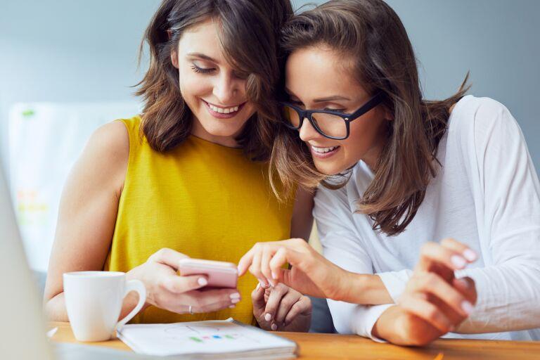 две девушки в бьюти-приложении выбирают подходящее косметическое средство