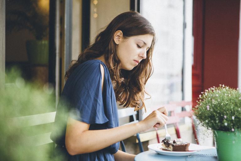 Девушка в кафе ест десерт.