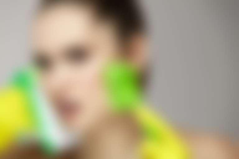 Девушка очищает кожу щетками, чтобы отбелить кожу от загара