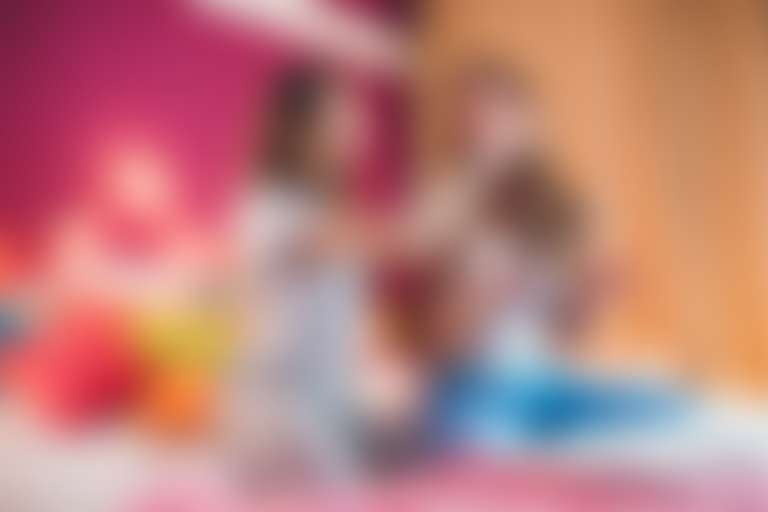 Девочки в пижамах на кровати наносят друг другу макияж