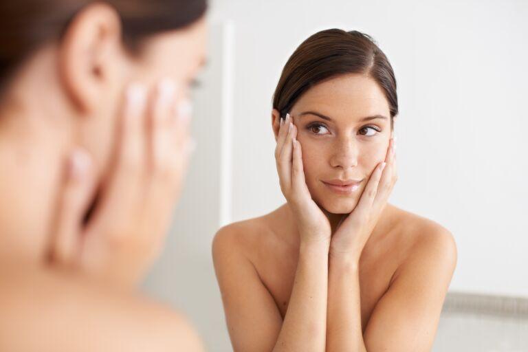 Девушка смотрится в зеркало, обхватив контур лица руками