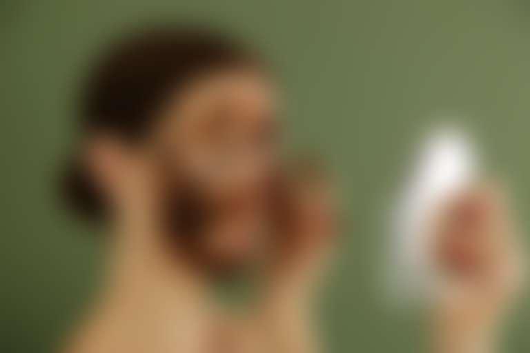 Девушка с кофейной гущей на лице смотрится в круглое настольное зеркало
