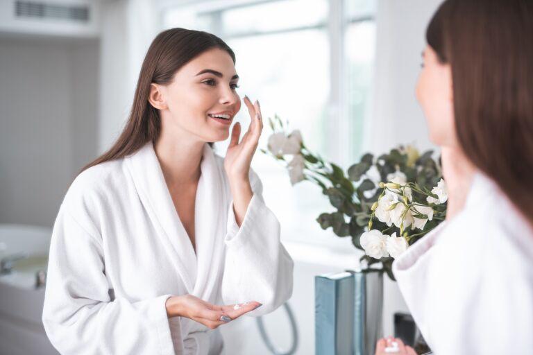 Девушка в белом банном халате смотрится в зеркало в ванной и наносит крем.