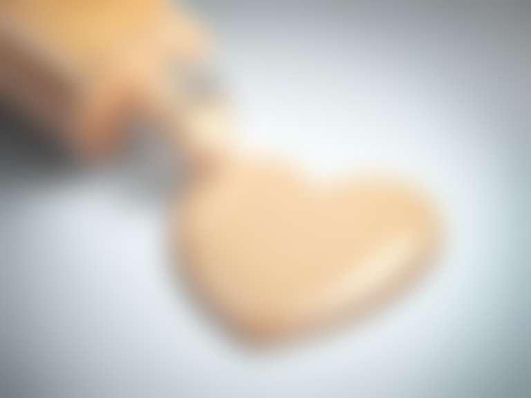 Из флакона выливается лужица BB-крема в форме сердечка