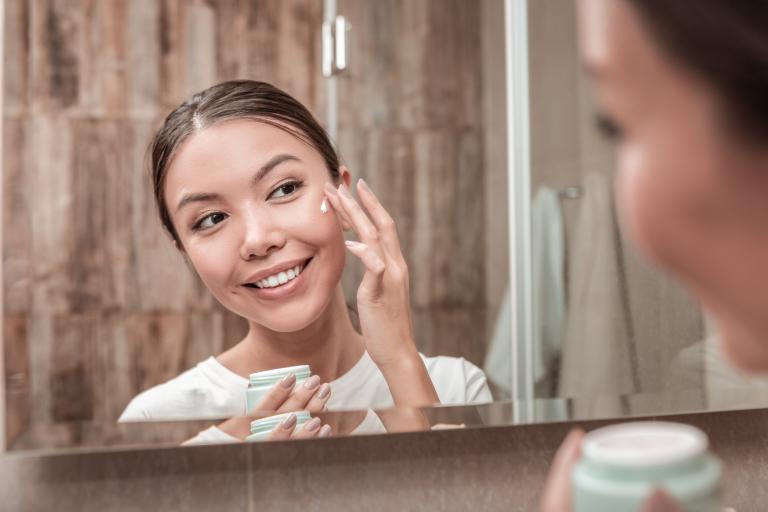 Девушка, нанеся на лицо крем, смотрится в зеркало и улыбается