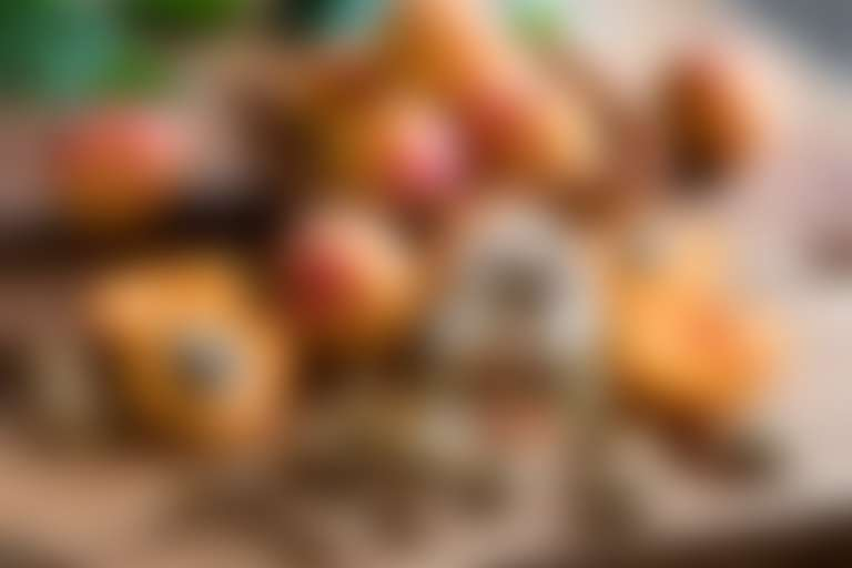 Нарезанные абрикосы на деревянном столе рядом со скляночками