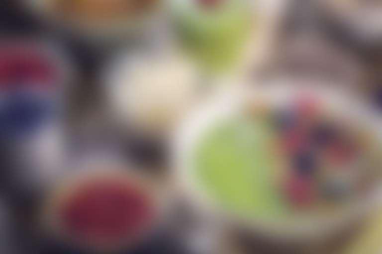Тарелки со смузи, кашей с фруктами и ягодами