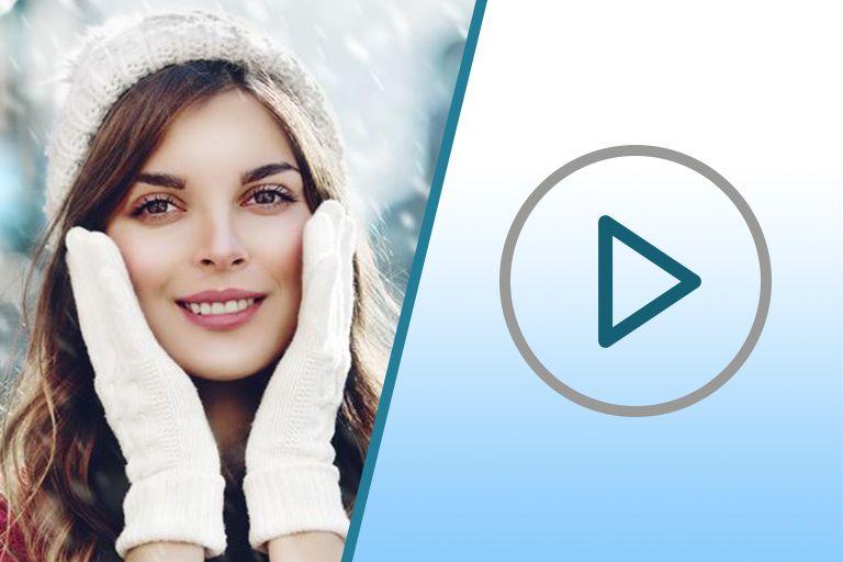 девушка с ухоженной кожей и легким макияжем, в белой вязаной шапке и белых перчатках на фоне снега