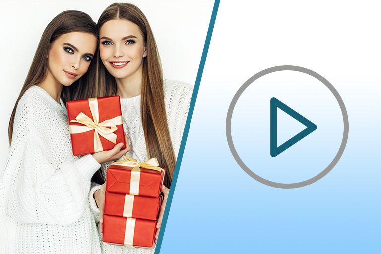 две девушки с ухоженной кожей и длинными волосами в белых свитерах с красными подарочными коробками