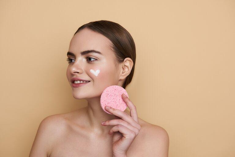 Девушка с кремом на лице в виде сердечка держит в руке розовый спонжик