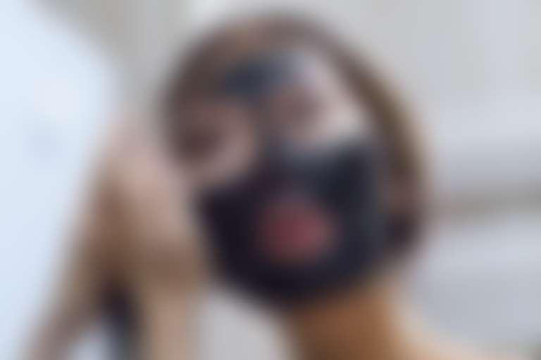 Азиатская девушка наносит черную маску на лицо